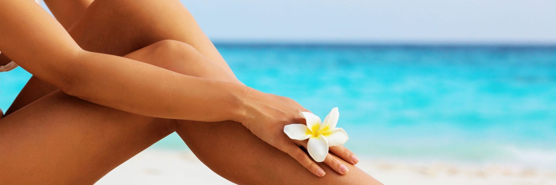 Frau am Strand mit Blume am Finger