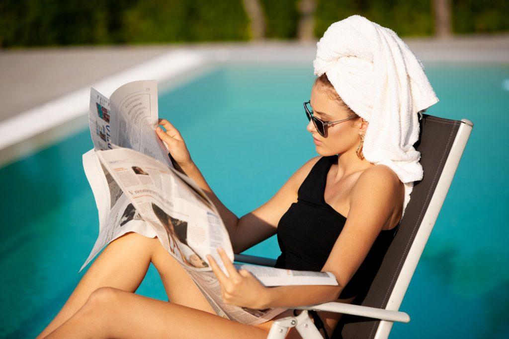 Zeitunglesende Frau am Pool